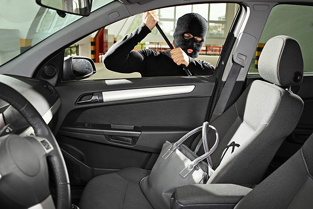 Thief trying to steal a purse bag in car