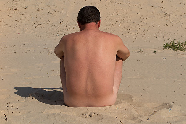 A naked man is sitting cross legged  on an empty beach and meditating.